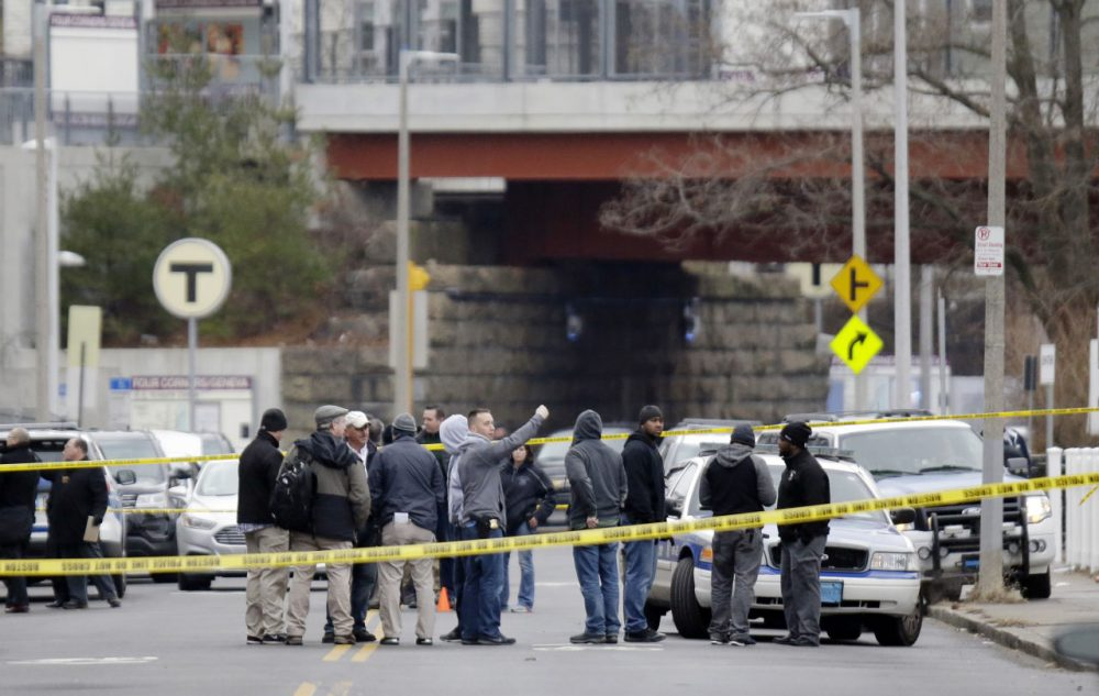Law enforcement officers gather near the scene where a Boston police officer was shot Friday morning in Dorchester. Police say the officer, who was shot in the leg after pulling over a known drug dealer, is expected to survive. (Stephan Savoia/AP)