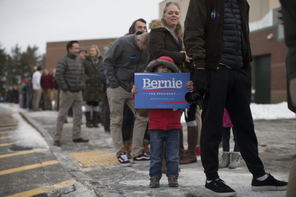 Sam Chausovsky holds a sign as attendees wait in line before a Bernie Sanders campaign event at Bedford High School last week. (John Minchillo/AP)