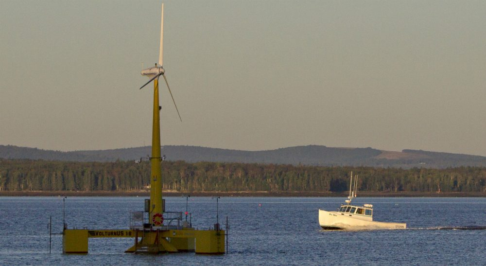 "Fred Hewett: ""The compelling logic of offshore wind makes you wonder what took us so long to catch on."" Pictured: A lobster boat passes the country's first floating wind turbine off the coast of Castine, Maine, which has been generating power since the summer of 2013. (Robert F. Bukaty/AP)"