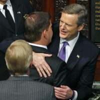 Charlie Baker, right, greets Boston Mayor Marty Walsh as he enters the House Chamber at the State House in Boston on Jan. 8, 2015 for his inauguration as governor of Massachusetts. (Elise Amendola/AP)