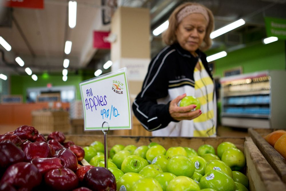 Noemi Sosa looks at an apple as she shops at the Daily Table, the first not-for-profit supermarket located in Dorchester. Dorchester Community Food Co-op would bring much-needed fresh food to the Four Corners neighborhood of Dorchester. (Jesse Costa/WBUR)
