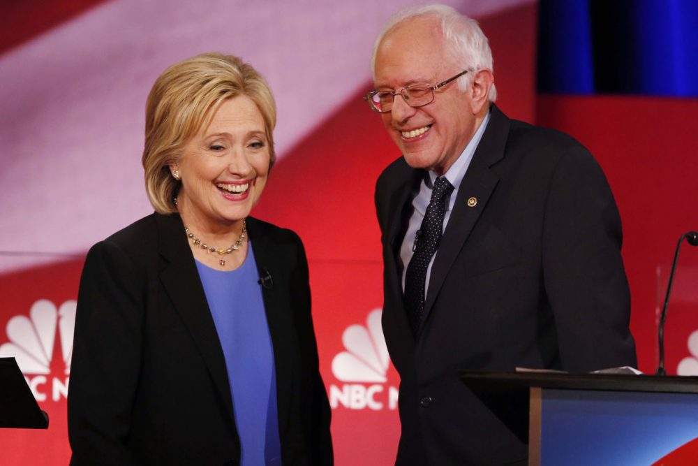Democratic presidential candidate, Hillary Clinton and Democratic presidential candidate, Sen. Bernie Sanders, I-Vt. smile during a break of the NBC, YouTube Democratic presidential debate at the Gaillard Center, Sunday, Jan. 17, 2016, in Charleston, S.C. (AP Photo/Mic Smith)