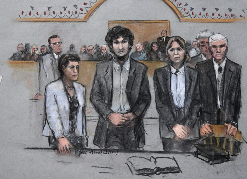 In this courtroom sketch, Boston Marathon bomber Dzhokhar Tsarnaev stands with his defense attorneys as a death by lethal injection sentence is read at the Moakley Federal court house in May. (Jane Flavell Collins/AP)