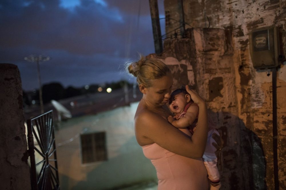 Gleyse Kelly da Silva, 27, holds her daughter Maria Giovanna, who was born with microcephaly, outside their house in Recife, Pernambuco state, Brazil. (Felipe Dana/AP)