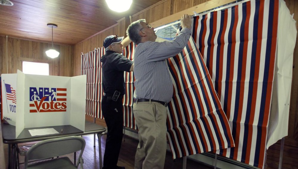 This year's presidential primary is the first in which New Hampshire's voters will be required to show identification before they can cast their ballots. Pictured here, Calab Pike, left, and Jack Parsons set up voting booths in Tuftonboro, New Hampshire, in 2014. (Jim Cole/AP)