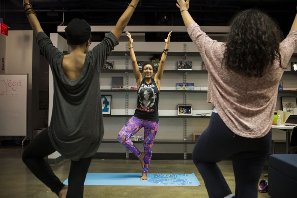 Twenty-four-year-old Chanelle John, center, last spring founded what she says is Boston's first yoga class for people of color. Here, she leads exercises in the South End. (Jesse Costa/WBUR)