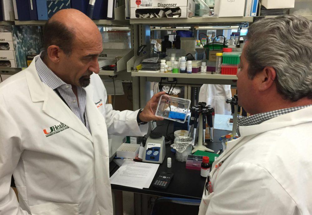 UM's Mario Stevenson (left) examines the new Zika virus detection test at his team's Miami lab. (Tim Padgett/WLRN)