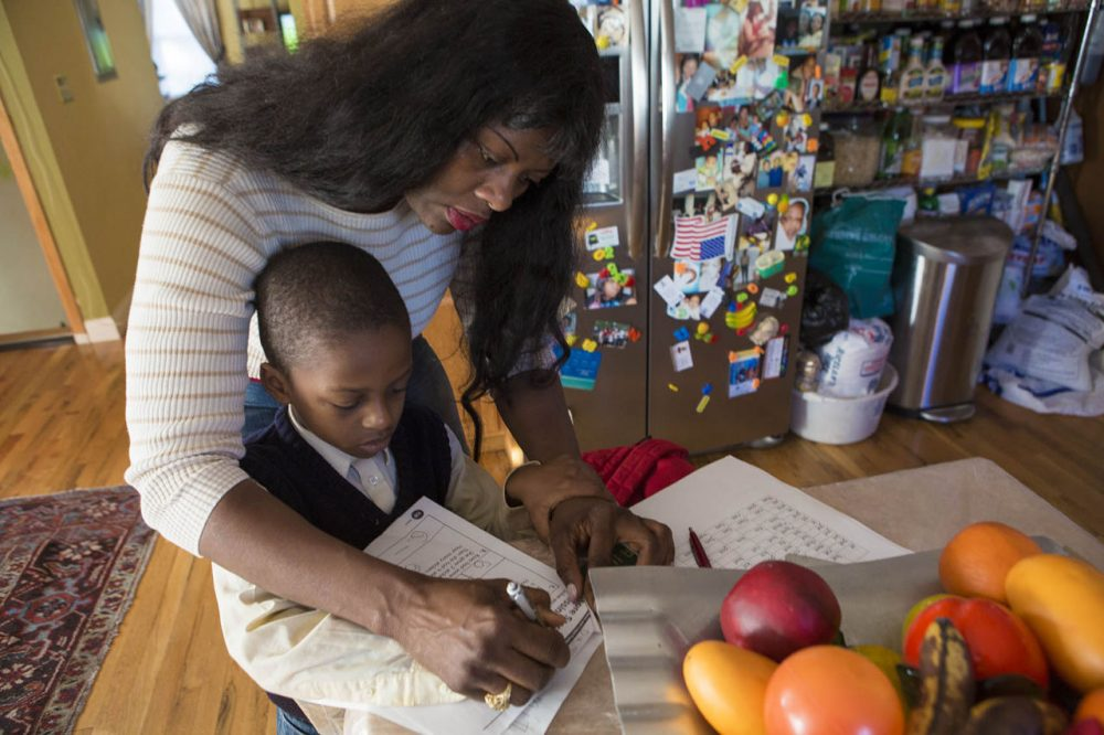 "Suzanne Bouffard: ""Kindergartners and preschoolers are counting on us to help them do and be their best. Ending suspensions is a vital step, but it's just the beginning."" Pictured: Delores Michel helps her son, Dashon, sign his homework assignment. The first grader was one of hundreds of Massachusetts children suspended from kindergarten last year. (Jesse Costa/WBUR)"