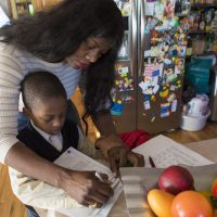 """Suzanne Bouffard: """"Kindergartners and preschoolers are counting on us to help them do and be their best. Ending suspensions is a vital step, but it's just the beginning."""" Pictured: Delores Michel helps her son, Dashon, sign his homework assignment. The first grader was one of hundreds of Massachusetts children suspended from kindergarten last year. (Jesse Costa/WBUR)"""