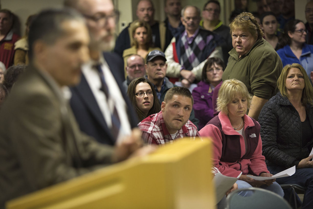 Dudley residents look on as attorney Jason Talerman, right, and civil engineer Imad Zrein present the Muslim cemetery plan for Corbin Road at a packed public hearing on Thursday evening. (Jesse Costa/WBUR)