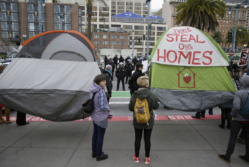 Demonstrators hold up tents during a protest to demand city officials do more to help homeless people outside Super Bowl City, a pro-football's weeklong theme park near the famed Ferry Building in San Francisco on Wednesday, Feb. 3, 2016. Dozens protested what they say is San Francisco Mayor Ed Lee's plan to push homeless people out of the scenic bay-front Embarcadero, where Super Bowl festivities are being held. (Eric Risberg/AP)
