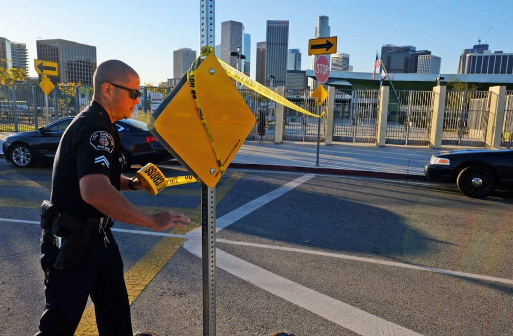 A police officer puts up yellow tape a high school in Los Angeles following an electronic threat to the district. Hoaxers are increasingly going online to threaten attacks against U.S. schools, and others. (Richard Vogel/AP)