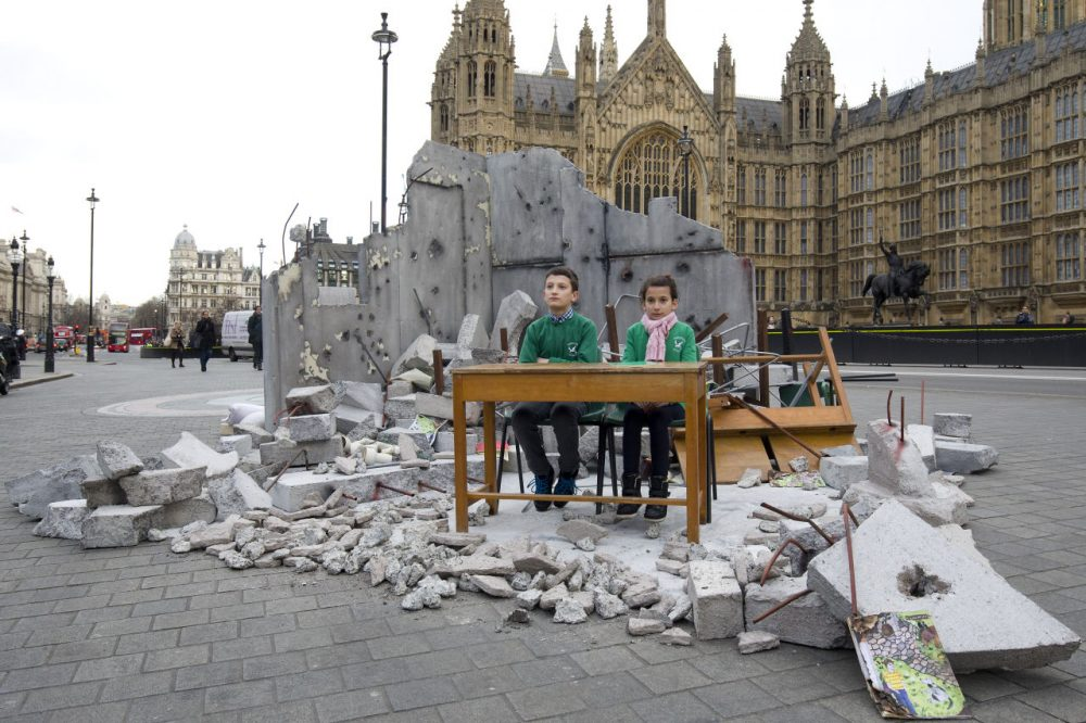 Two children whose school was bombed in Aleppo pose in a mock-up meant to symbolize a destroyed classroom, set up by charity Save the Children outside the Houses of Parliament in London on February 3, 2016 on the eve of a donor conference aiming to raise money for the millions of Syrians hit by the country's civil war and a refugee crisis. (Justin Tallis/AFP/Getty Images)