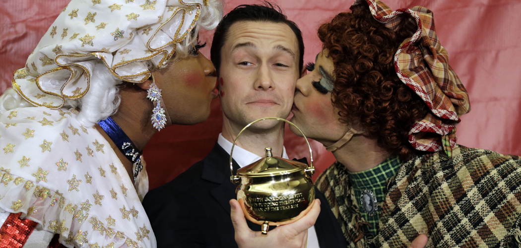 Actor Joseph Gordon-Levitt is kissed by two actors in drag after being awarded the pudding pot as Harvard University's Hasty Pudding Theatricals Man of the Year on Friday, Feb. 5, 2016. (Elise Amendola/AP)