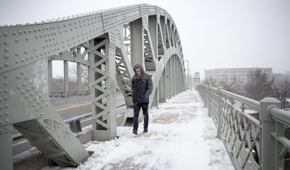 "James Bridger, 22, crosses BU Bridge in Boston during Monday's storm. He's visiting Boston from the United Kingdom and when asked about the weather here, said, ""I've seen better."" (Robin Lubbock/WBUR)"