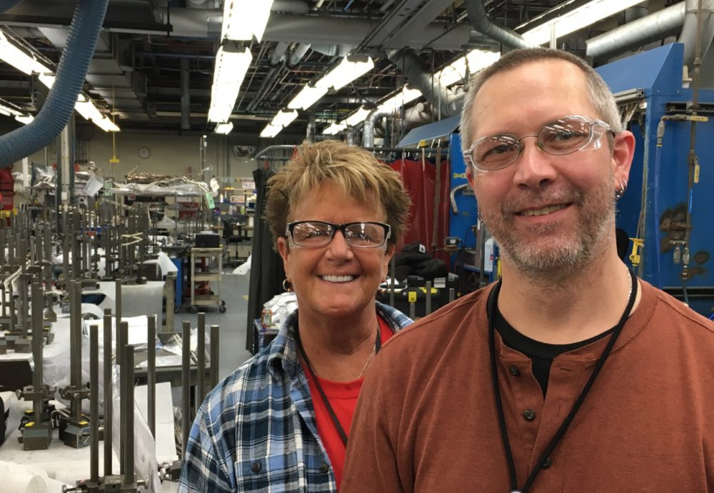 GE employees Debbie Birdsey (left) and Brad Slayton pose for a photo at the Hooksett, N.H., plant. Birdsey is retiring in coming months and has mixed feelings. She said she felt lucky to work where she does. But the factory is struggling to attract young workers. (Jill Ryan/Here & Now)