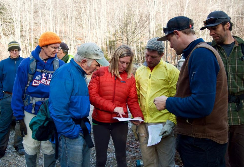 Green Mountain National Forest's Holly Knox, center, and trail designer Hardy Avery, second from right, go over maps that show new backcountry ski trails. Dozens of volunteers have spent the last several weeks clearing trees and brush along the trails. (Nina Keck/VPR)