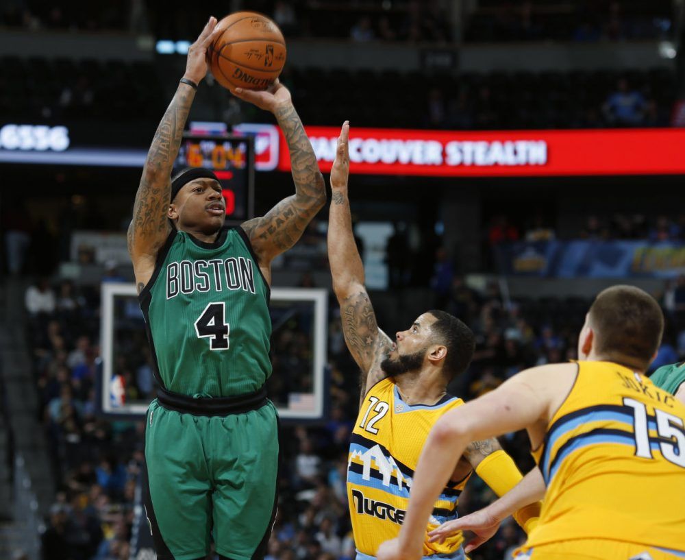 Celtics guard Isaiah Thomas goes up for a three-point basket over Nuggets guard D.J. Augustin, center, and center Nikola Jokic, in a game Sunday, Feb. 21, 2016, in Denver. (David Zalubowski/AP)