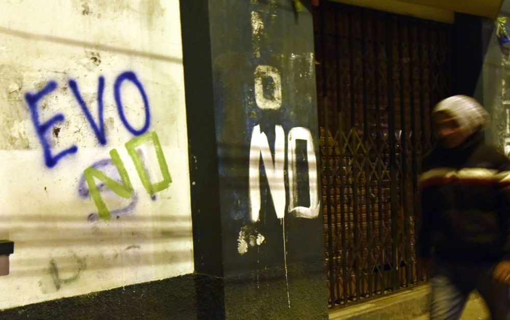 "A man is seen walking next to a graffiti that reads ""Evo no"" after the referendum rejection in El Alto, Bolivia, on February 21. Bolivians on Sunday rejected leftist President Evo Morales' bid to seek a fourth term and potentially extend his presidency until 2025, local media reported. (Aizar Raldes/AFP/Getty Images)"