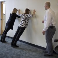 Fitness expert Rick DiScipio watches as WBUR staff do wall push-ups. (Robin Lubbock/WBUR)