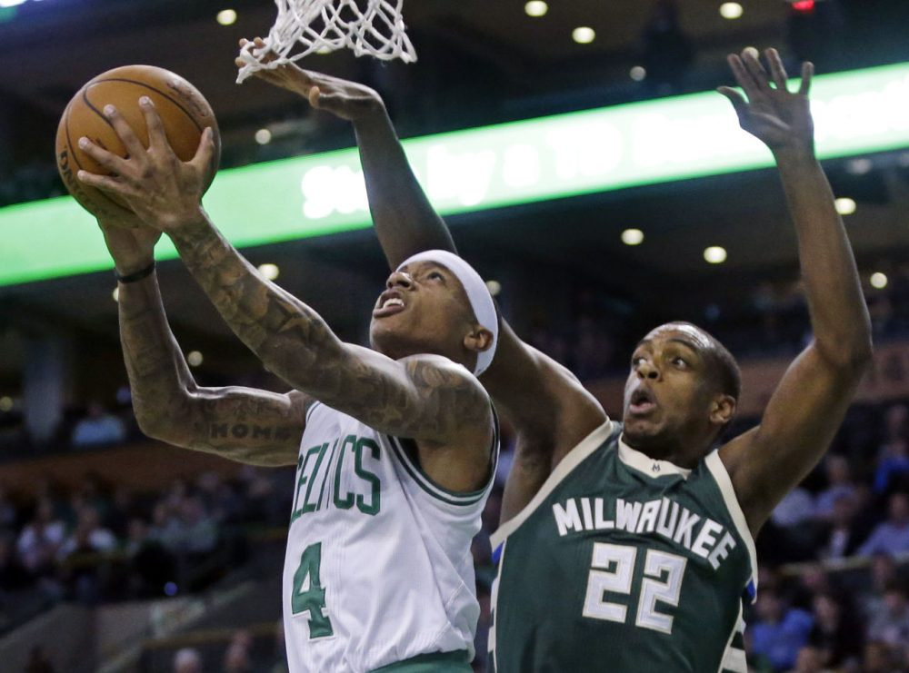 Boston Celtics guard Isaiah Thomas (4) puts up a reverse layup against the defense of Milwaukee Bucks guard Khris Middleton (22) during last night's game. (Elise Amendola/AP)