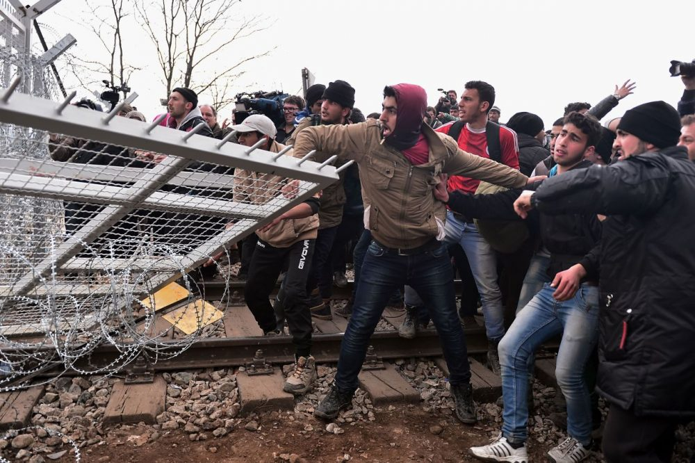 "Refugees break into the Greek-Macedonian borders during their protest demanding the opening of the borders near the village of Idomeni on February 29, 2016.  Macedonian police fired tear gas on February 29, 2016, as a group of some 300 Iraqi and Syrians forced their way through a Greek police cordon and raced towards a railway track between the two countries. With Austria and Balkan states capping the numbers of migrants entering their soil, there has been a swift buildup along the Greece-Macedonia border with Athens warning that the number of people ""trapped"" could reach up to 70,000 by next month.  (Louisa Gouliamaki/AFP/Getty Images)"