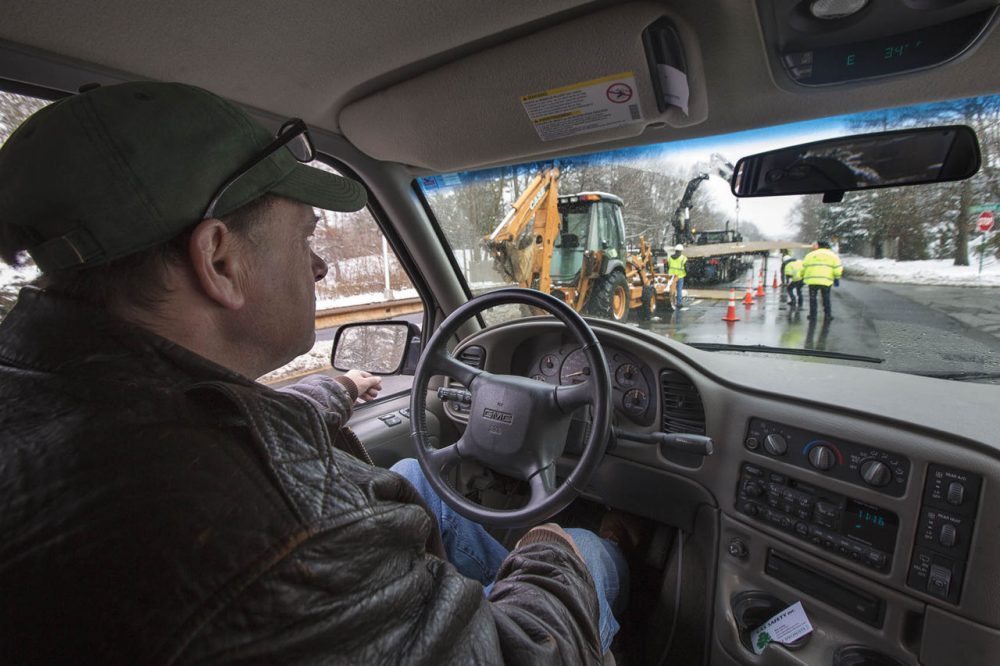 """The gas company is working right up ahead of us right now repairing a leak,"" said Bob Ackley, of Gas Safety USA, as he drives a van that is equipped to detect and map methane leaks. Most of the small leaks Ackley detects pose no danger, but unseen and strikingly common, experts estimate they account for 10 percent of all greenhouse gases emitted in the state. (Jesse Costa/WBUR)"