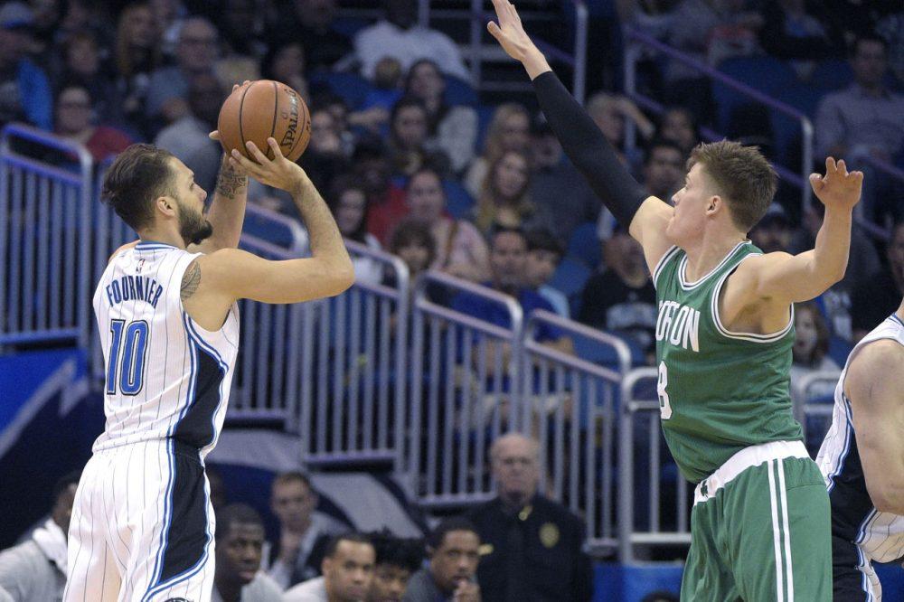 Magic guard Evan Fournier puts up a three-pointer in front of Celtics forward Jonas Jerebko during Sunday's game in Orlando. The Magic won 119-114. (Phelan M. Ebenhack/AP)
