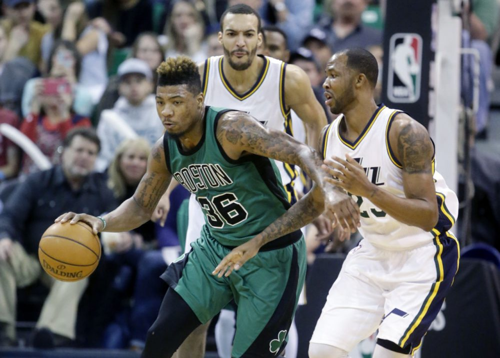 Celtics guard Marcus Smart (36) drives around Utah Jazz's Chris Johnson, right, as Rudy Gobert, rear, looks on during Friday night's game in Salt Lake City. (Rick Bowmer/AP)