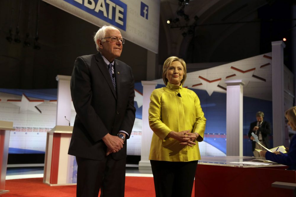 A WBUR poll finds Hillary Clinton leads her presidential primary rival, Bernie Sanders, among likely Democratic voters in Massachusetts. Here, Sanders and Clinton are seen before a Feb. 11 debate in Milwaukee. (Tom Lynn/AP)