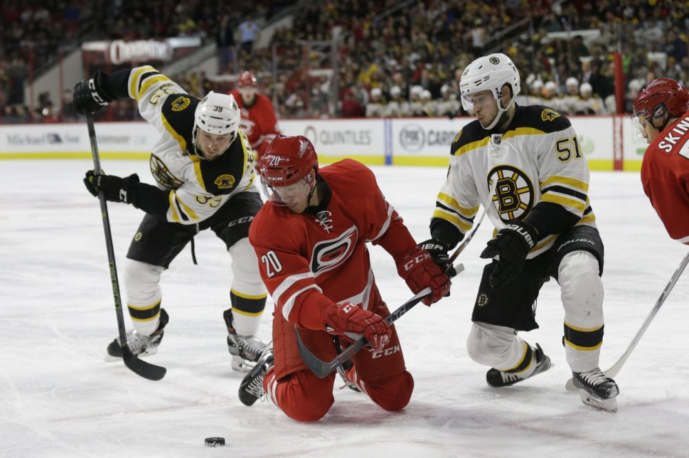 Bruins' Matt Beleskey (39) and Ryan Spooner (51) struggle with Carolina Hurricanes' Riley Nash (20) during a game in Raleigh, North Carolina Friday night. (Gerry Broome/AP)