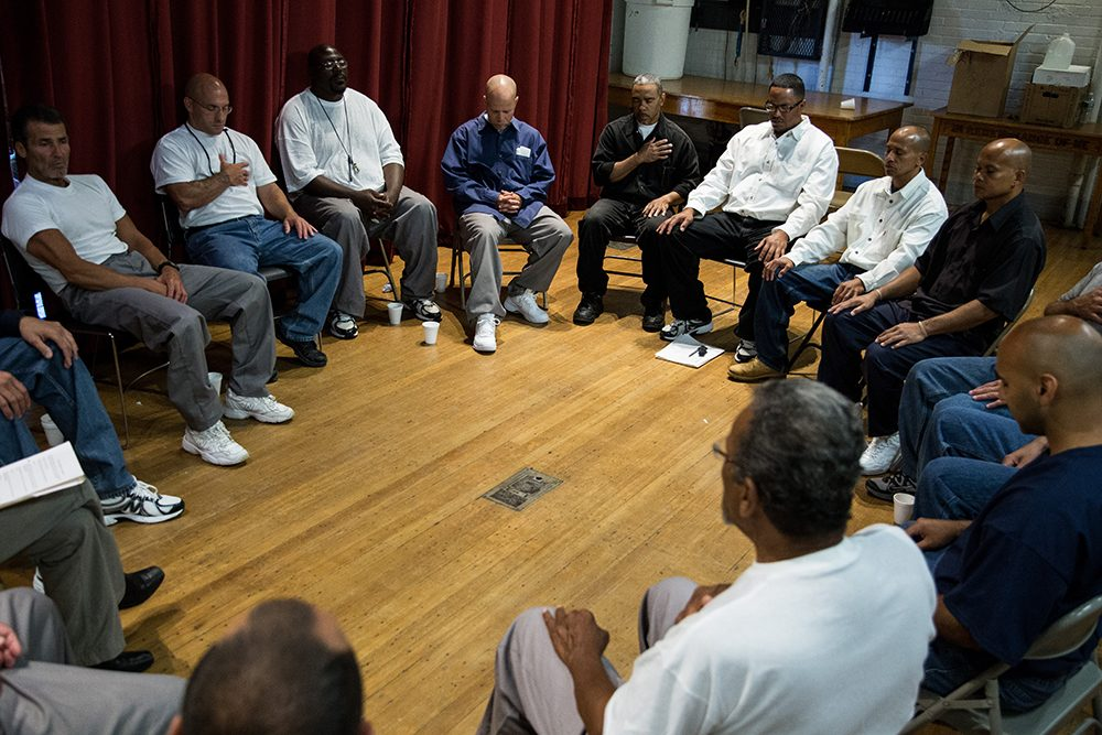 Inmates participate in a group meditation prior to a discussion during a Restorative Justice and Responsibility Retreat at MCI Norfolk in 2014. Restorative justice focuses on making amends, bringing victims and offenders of crimes together in mediated dialogue. (Courtesy Charlie Mahoney)