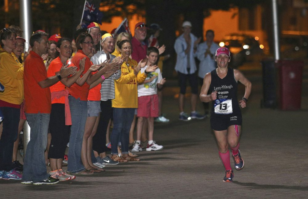 Becca Pizzi runs past supporters as she nears the finish line in the seventh and final leg of the the World Marathon Challenge Saturday in Sydney, Australia. (AP Photo/Rob Griffith)