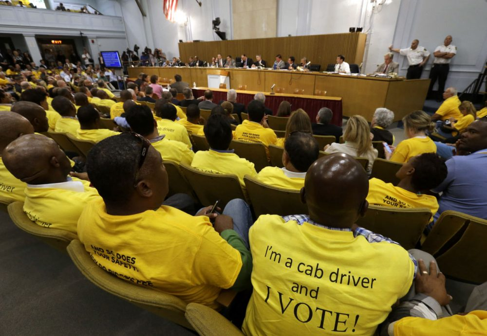 Taxi drivers wearing yellow tee shirts with written messages sit together during a hearing on the regulation of ride handling companies such as Uber and Lyft,  Sept. 15, 2015, at the Statehouse. (Steven Senne/AP)