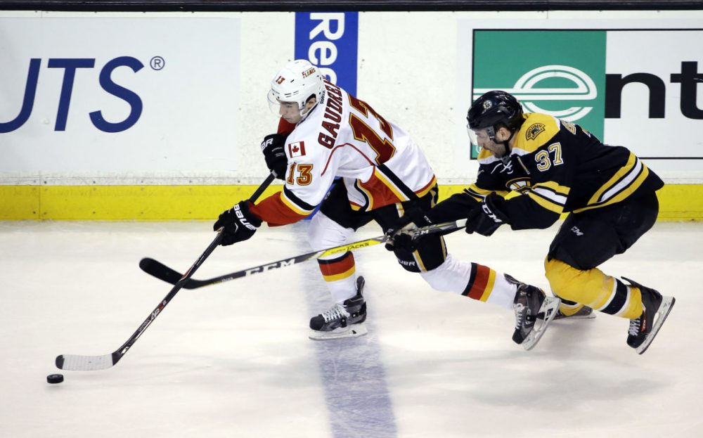 Flames left wing Johnny Gaudreau controls the puck as Bruins center Patrice Bergeron chases him in the third period, Tuesday, March 1, 2016, in Boston. (Elise Amendola/AP)