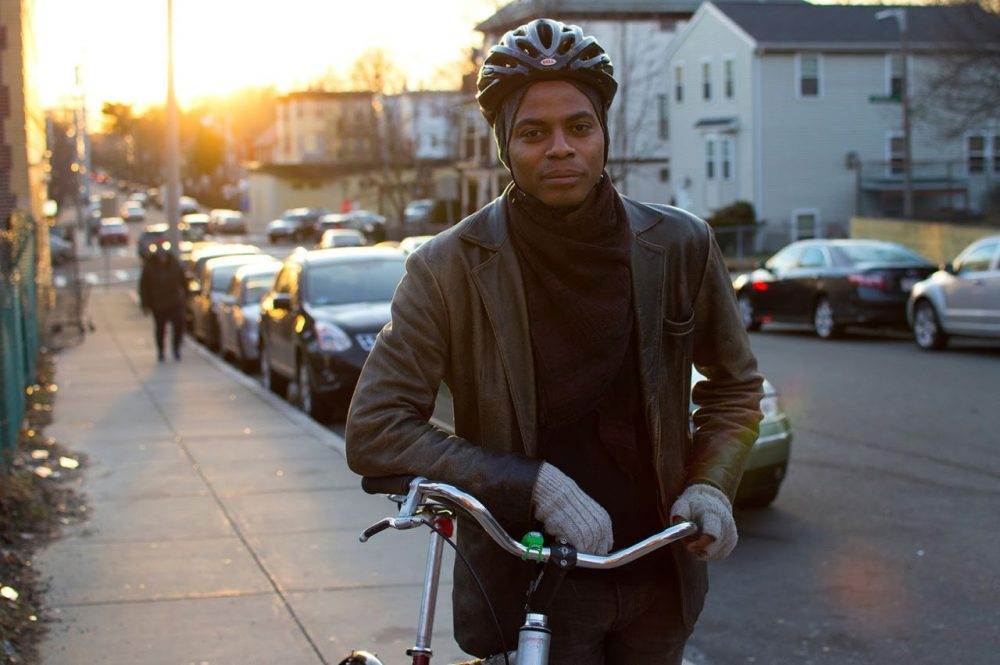 Noah Hicks stands with his bike outside Bowdoin Bike School on Southern Ave in Dorchester. (Hadley Green for WBUR)