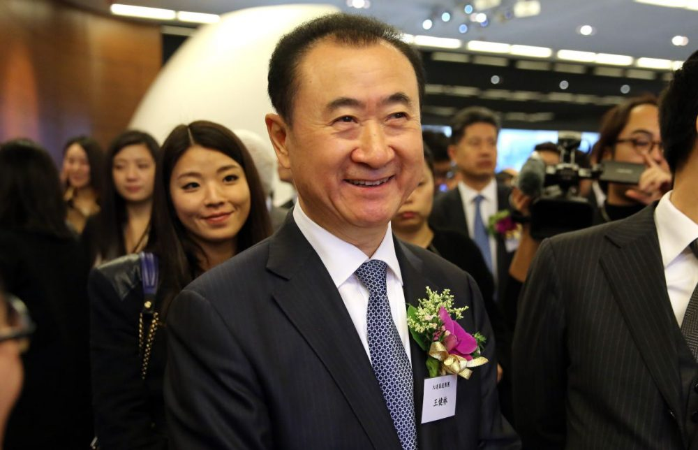 Wang Jianlin (center), CEO of Dalian Wanda Commercial Properties Co Ltd, arrives before the company's IPO at the Hong Kong Stock Exchange in the Central district of Hong Kong on December 23, 2014. Wang Jianlin rose from local bureaucrat to China's richest man by transforming a debt-laden state-owned housebuilder into the sprawling Wanda Group, and the flotation of one of its subsidiaries on December 23 may propel him back up a rich list now dominated by Internet moguls. (Isaac Lawrence/AFP/Getty Images)