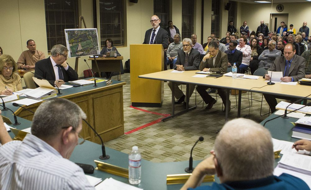 Representing the Islamic Center of Greater Worcester, attorney Jason Talerman (standing) addresses the Dudley Zoning Board in front of a packed room Thursday night. (Jesse Costa/WBUR)