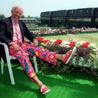 Sports journalist Bud Collins displays a pair of brightly-colored trousers as he sits overlooking the outside courts at Wimbledon in 1993. One of the country's foremost authorities on professional tennis, Collins died Friday, March 4, 2016 at his home in Brookline. He was 86. (Gill Allen/AP)