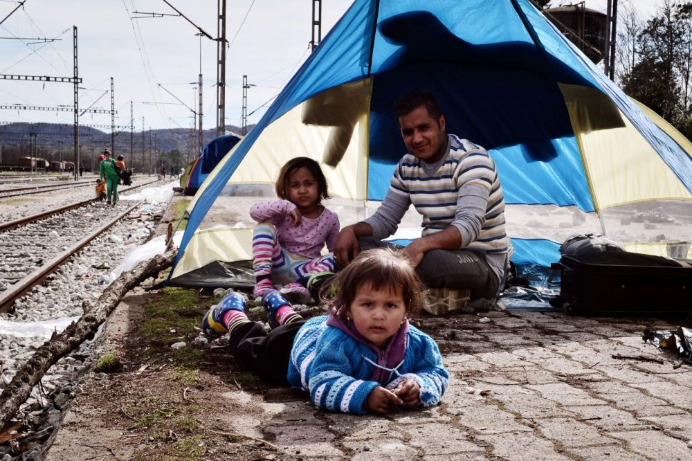 A family sits at the makeshift camp at the Greek-Macedonian border, near the village of Idomeni on March 8, 2016, where thousands of refugees and migrants are stranded. European Unions leaders held a summit with Turkey's prime minister on March 7 in order to back closing the Balkans migrant route and urge Ankara to accept deportations of large numbers of economic migrants from overstretched Greece. More than one million refugees and migrants have arrived in Europe since the start of 2015 -- the majority fleeing the war in Syria -- with nearly 4,000 dying while crossing the Mediterranean. (Louisa Gouliamaki/AFP/Getty Images)
