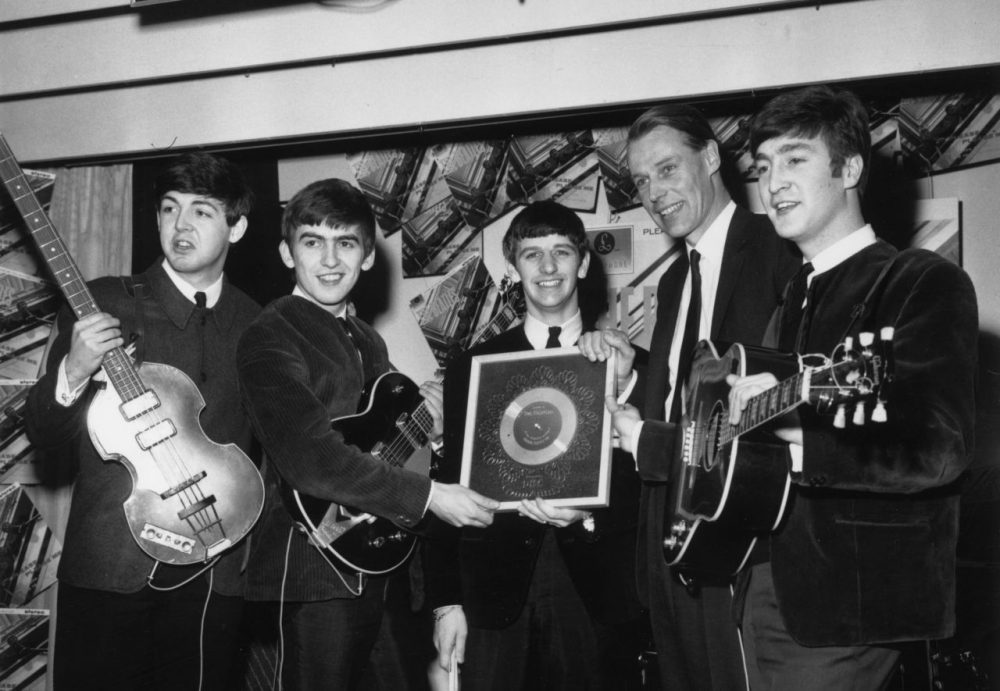 "The Beatles hold their silver disc for sales of more than 250,000 copies of their debut studio album ""Please, Please Me"" on April 8, 1963. Left to right are, Paul McCartney, George Harrison (1943 - 2001), Ringo Starr, George Martin of EMI and John Lennon (1940 - 1980). (Chris Ware/Keystone/Getty Images)"
