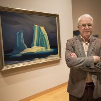 """Steve Martin is curating a new show about Canadian modernist painter Lawren Harris. Here, Martin stands in front of Harris' """"Icebergs,"""" on display at the Museum of Fine Arts in Boston. (Jesse Costa/WBUR)"""