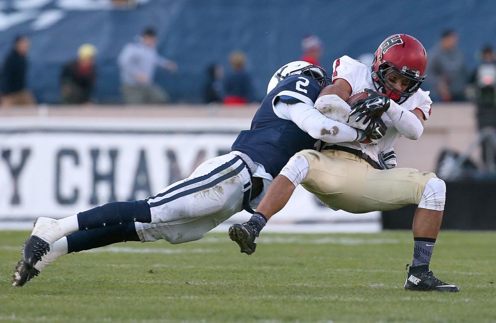 Andrew Fischer #1 of the Harvard Crimson gains yards against the defense of Marquise Peggs #2 of the Yale Bulldogs in the first half on November 21, 2015 in New Haven, Connecticut. (Jim Rogash/Getty Images)