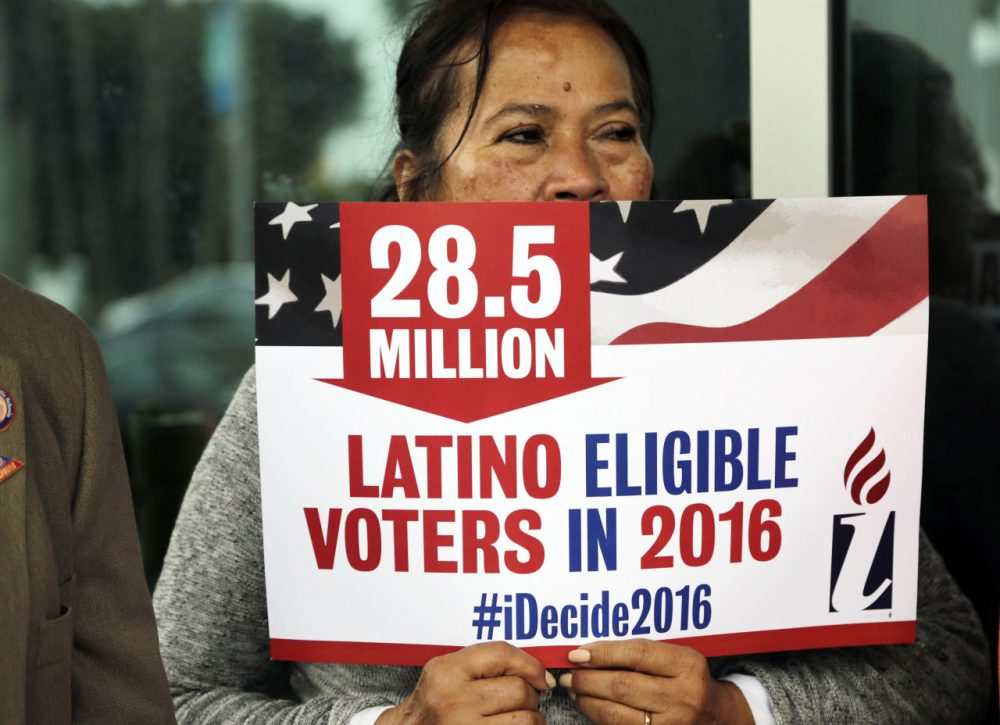 Georgina Arcienegas holds a sign in support of Latino voters during a protest outside the office of Florida Rep. Carlos Trujillo, Tuesday, Jan. 12, 2016, in Doral, Fla. (Lynne Sladky/AP)