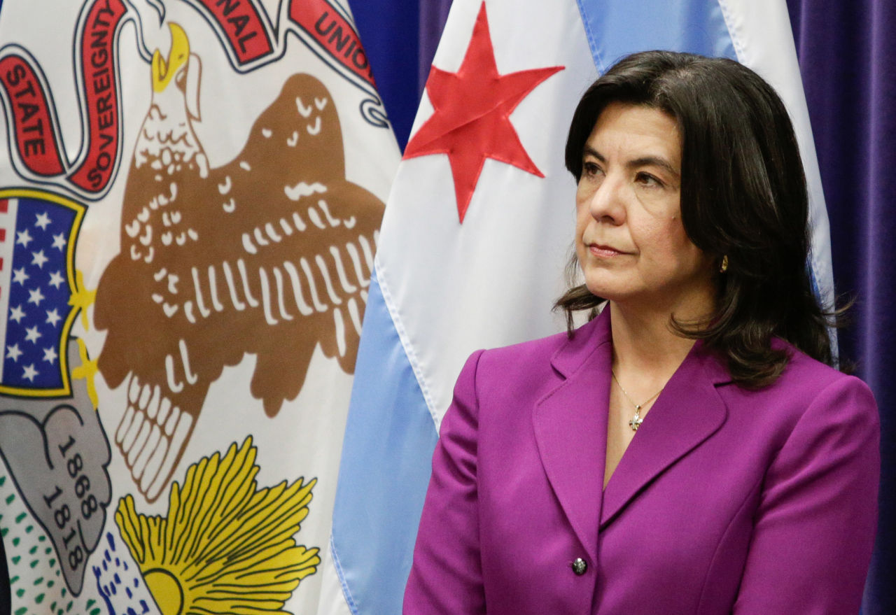 Cook County State's Attorney Anita Alvarez listens as Interim Chicago Police Superintendent John Escalante speaks at a news conference Tuesday, March 8, 2016, in Chicago. Escalante said a Chicago man has been charged with first-degree murder, after police say he helped lure a 9-year-old boy into an alley with a juice box late last year and then shot him in the head because of his father's gang ties. Dwright Boone-Doty was charged Monday night in the Nov. 2 death of Tyshawn Lee. Alvarez said Boone-Doty shot the boy several times at close range. (AP Photo/Teresa Crawford)