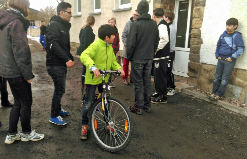 Ramzi, 13, from Lebanon tries out his new bicycle as volunteers and other newly arrived residents in Clausnitz look on. (Marc Lalonde)
