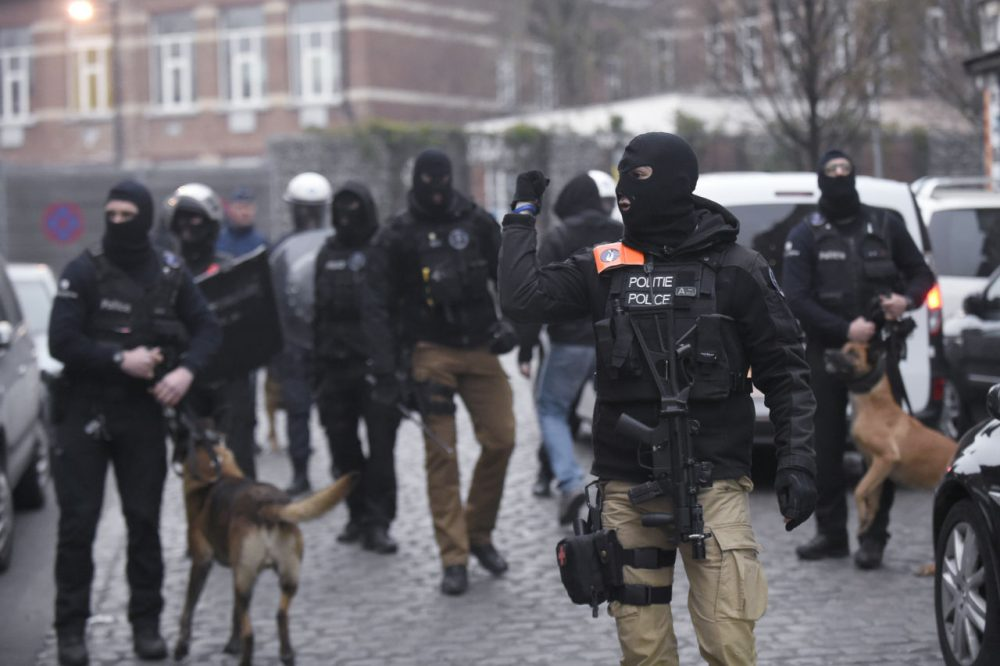 Belgian policemen walk in a street during a police action in the Molenbeek-Saint-Jean district in Brussels, on March 18, 2016. (John Thys/AFP/Getty Images)