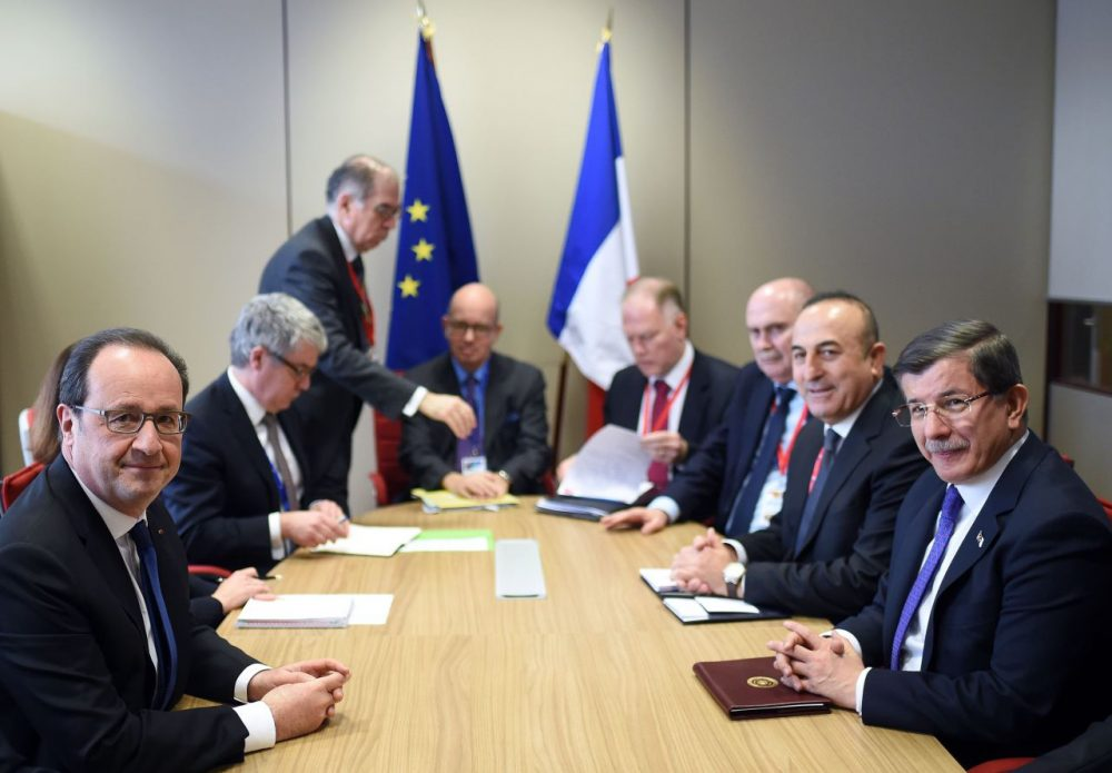 French President Francois Hollande (left) meets with Turkish Prime Minister Ahmet Davutoglu (right) and Foreign Minister Mevlut Cavusoglu (second from right) on the second day of a European Union summit to discuss the ongoing migrant crisis, in Brussels, on March 18, 2016. (Stephanie de Sakutin/AFP/Getty Images)