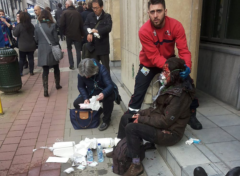 "A private security guard helps a wounded women outside the Maalbeek metro station in Brussels on March 21, 2016 after a blast at this station located near the E.U. institutions. Belgian firefighters said at least 26 people had died after ""enormous"" blasts rocked Brussels airport and a city metro station today, as Belgium raised its terror threat to the maximum level. (Michael Villa/AFP/Getty Images)"