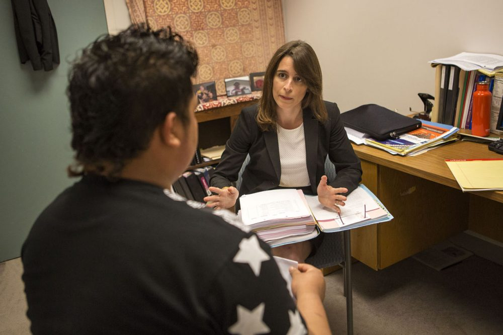 Sarah Sherman-Stokes, a clinical teaching fellow at the Boston University Immigrants' Rights Clinic, instructs a young client from El Salvador about his next appointment in immigration court. (Jesse Costa/WBUR)